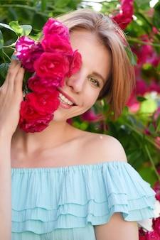 Ritratto di una bella ragazza rossa vestita con un abito a luce bianca su uno sfondo di rose in fiore