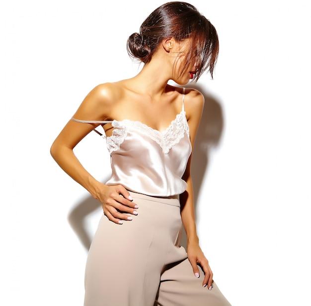 Ritratto di una bella ragazza sensuale donna bruna in eleganti abiti classici bianchi e pantaloni larghi su sfondo bianco