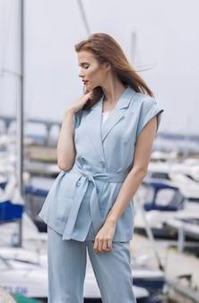 Ritratto di una bella signora elegante al molo pieno di yacht in estate.