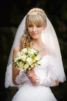 Ritratto di una bella sposa bionda con bouqet di nozze nelle mani