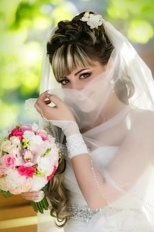 Ritratto di una bella sposa con un mazzo di fiori