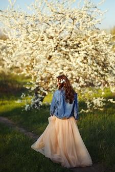 Ritratto di una bella sposa. concetto di matrimonio. matrimonio elegante. ottima luce del tramonto. indossa una giacca di jeans blu, vestito. giardino fiorito di primavera.
