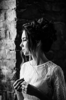 Ritratto di una bella sposa. spese di mattina a casa vicino al muro di mattoni. matrimonio classico. foto in bianco e nero