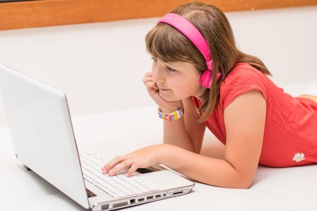 Ritratto di una bella studentessa che guarda e ascolta tutorial video in linea con le cuffie