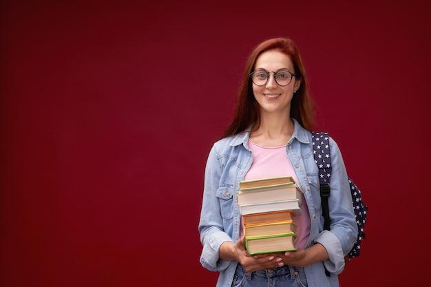Ritratto di una bella studentessa con uno zaino e una pila di libri in mano sorride