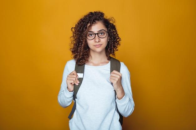 Ritratto di una bella studentessa indiana con uno zaino e occhiali.
