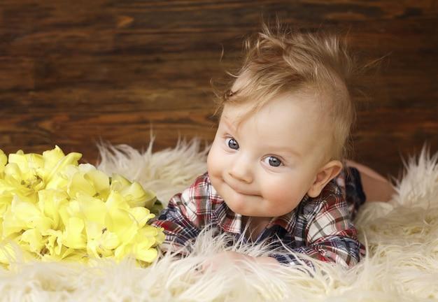 Ritratto di una bellissima bambina che giaceva a pancia in giù vicino a tulipani gialli, occhi grandi.