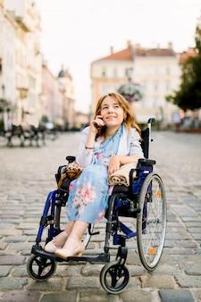 Ritratto di una bellissima giovane donna bionda in sedia a rotelle, godendo la sua giornata e parlando al telefono mentre si cammina in città all'aperto