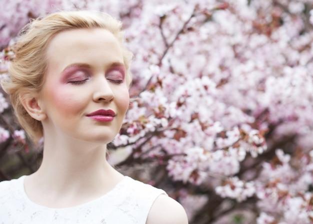 Ritratto di una bellissima giovane donna bionda su uno sfondo di fiori di ciliegio rosa in primavera