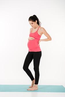 Ritratto di una bellissima giovane donna incinta in abito sportivo