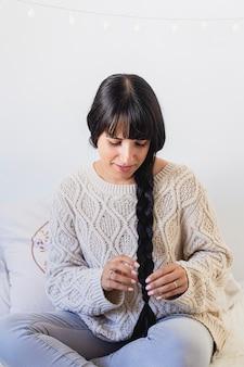 Ritratto di una bellissima giovane donna sorridente e facendo una treccia tra i capelli in abito invernale a casa