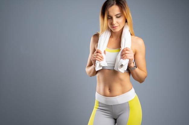 Ritratto di una bellissima giovane donna sportiva contro il grigio