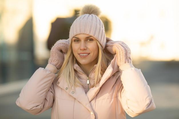 Ritratto di una bellissima giovane modella in rosa cappello lavorato a maglia e guanti. bella giovane donna bionda sorridente naturale che indossa i guanti tricottati.