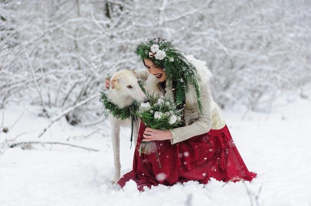 Ritratto di una bellissima giovane sposa che gioca con un cane da caccia. cerimonia nuziale invernale.