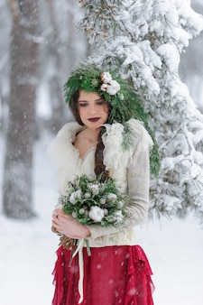 Ritratto di una bellissima giovane sposa con un bouquet. cerimonia nuziale invernale.