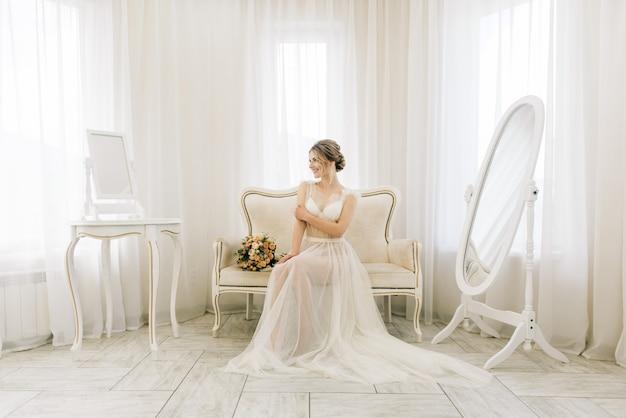 Ritratto di una bellissima giovane sposa in una stanza luminosa in un'atmosfera romantica. sposa in vestaglia con un mazzo di nozze