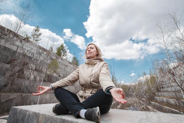 Ritratto di una bionda meditating all'aperto