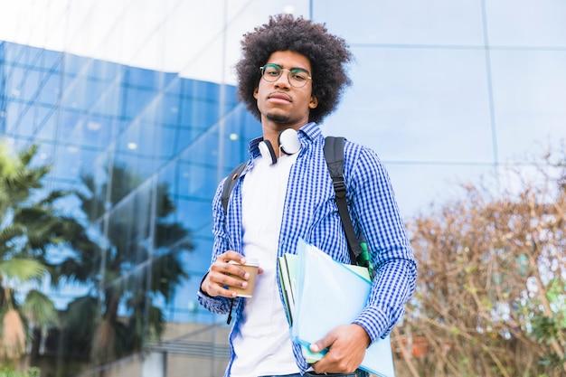 Ritratto di una borsa di trasporto del giovane studente afro americano maschio sulla spalla e sui libri a disposizione che stanno contro la costruzione dell'università