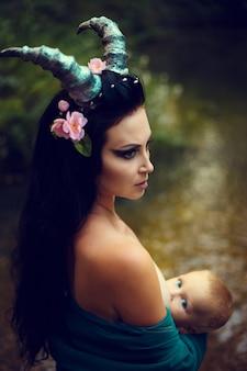 Ritratto di una bruna con una corona floreale in testa, corna nella foresta.