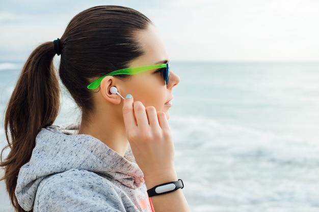 Ritratto di una brunetta in abbigliamento sportivo e occhiali da sole, si infila le cuffie e guarda il mare
