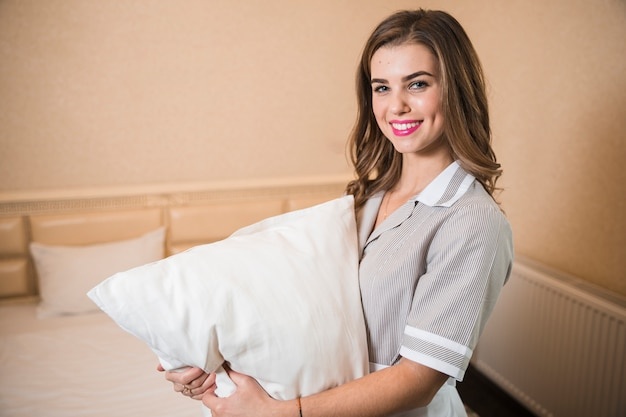 Ritratto di una cameriera sorridente che tiene morbido cuscino bianco in mano