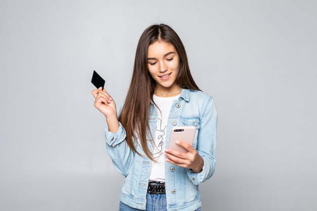 Ritratto di una carta di credito sorridente della tenuta della giovane donna isolata sopra la parete bianca