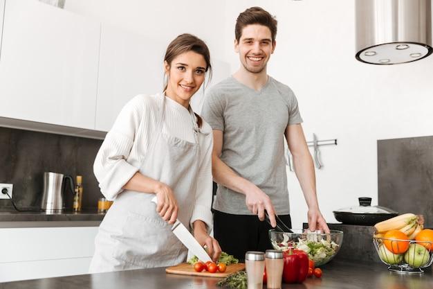 Ritratto di una coppia abbastanza giovane che cucina insieme