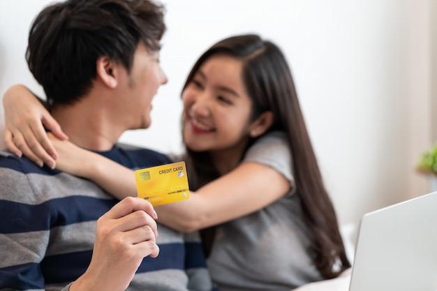 Ritratto di una coppia allegra asiatica che compera online con il computer portatile mentre sedendosi. uomo che tiene la carta di credito