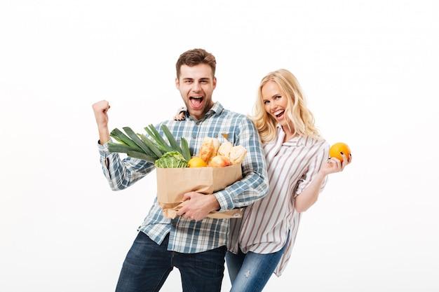 Ritratto di una coppia allegra che tiene il sacchetto della spesa di carta