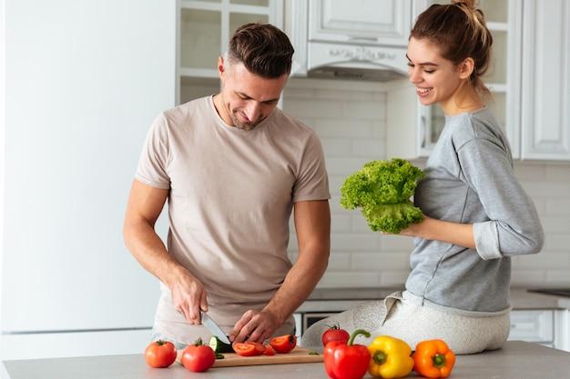 Ritratto di una coppia amorosa felice che cucina insieme insalata