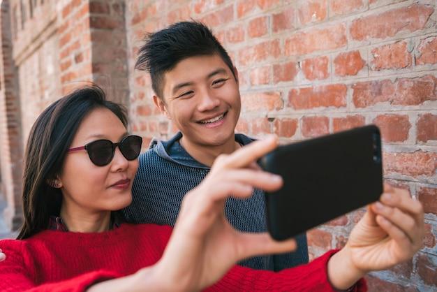 Ritratto di una coppia asiatica adorabile che cattura un selfie con il telefono cellulare all'aperto in strada