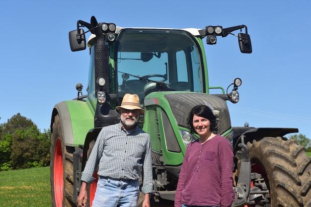 Ritratto di una coppia e di un trattore dell'agricoltore sul campo
