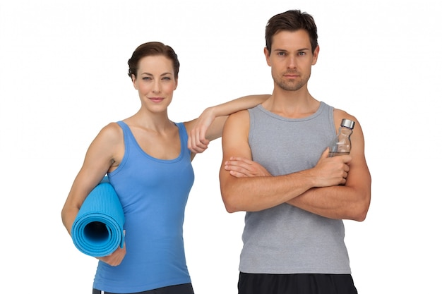 Ritratto di una coppia in forma con materassino e bottiglia d'acqua