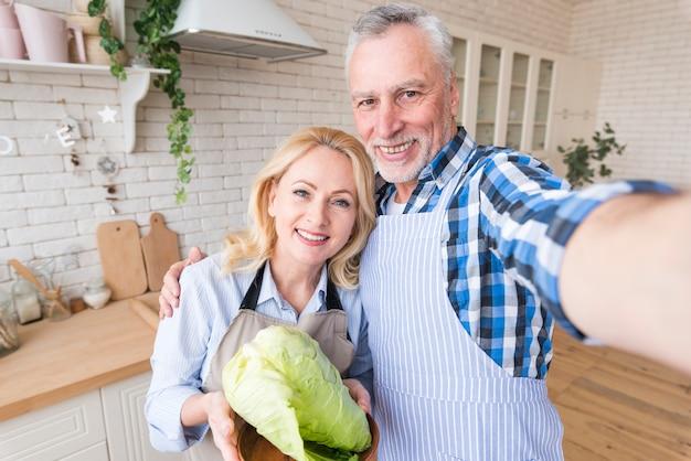 Ritratto di una coppia senior che prende selfie sul telefono cellulare nella cucina