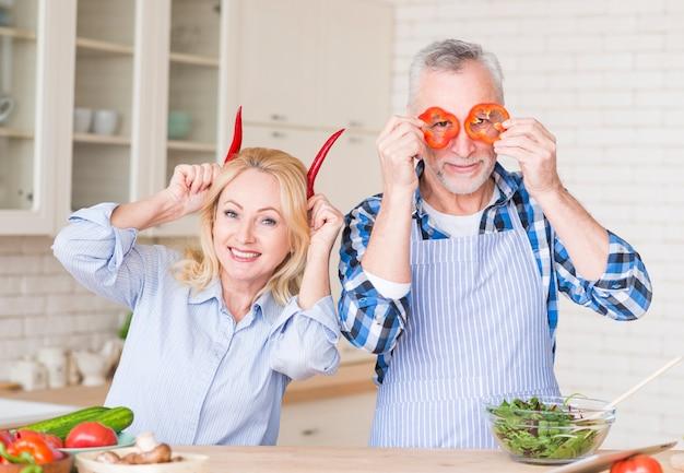 Ritratto di una coppia senior che tiene i peperoncini e peperoni dolci rossi che esaminano macchina fotografica nella cucina