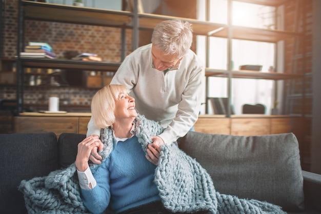 Ritratto di una coppia senior felice a casa. lei è seduta sul