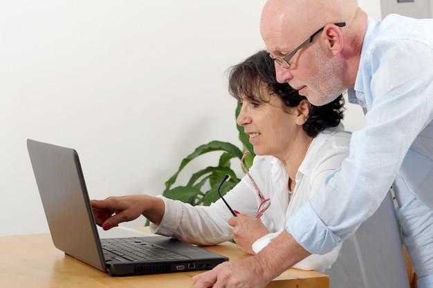 Ritratto di una coppia senior felice facendo uso del computer portatile