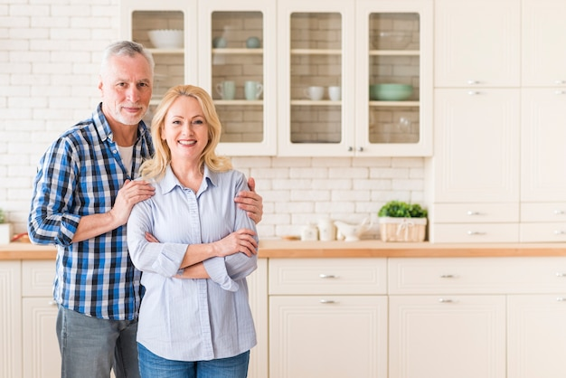 Ritratto di una coppia senior sorridente che sta nella cucina che esamina macchina fotografica