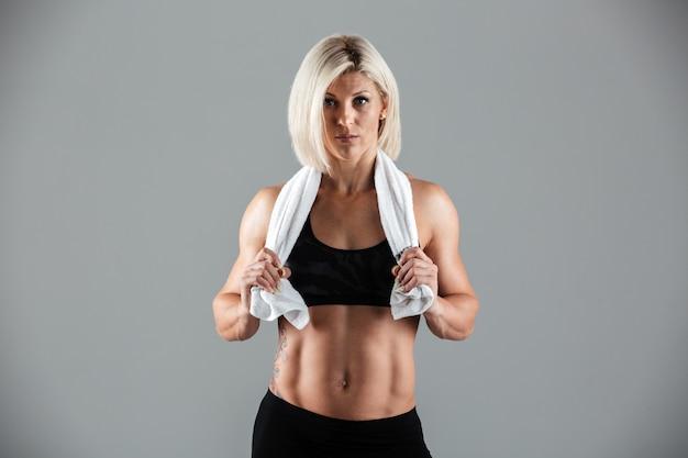 Ritratto di una donna adulta muscolare adatta che tiene un asciugamano