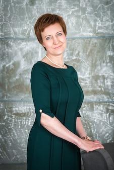 Ritratto di una donna affascinante sorridente in piedi con le braccia conserte e alla ricerca
