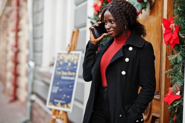 Ritratto di una donna africana dai capelli ricci che indossa cappotto nero alla moda e dolcevita rosso che posa porta vicina all'aperto con la decorazione di natale, notte di san silvestro. parla al telefono.