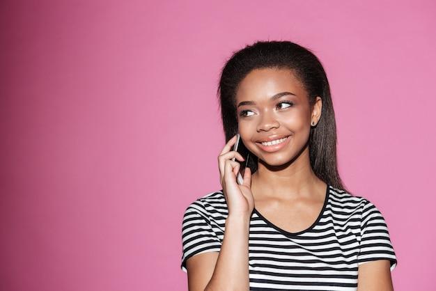 Ritratto di una donna africana sorridente che parla sul telefono cellulare