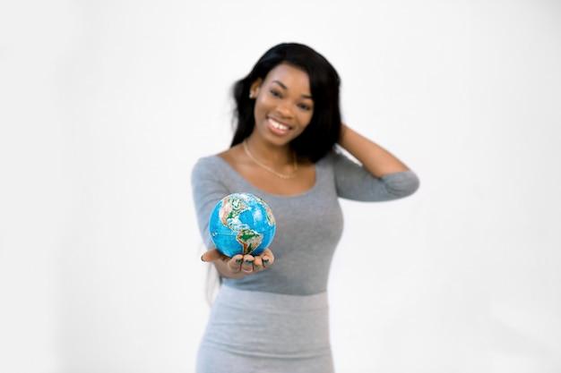 Ritratto di una donna africana sorridente che tiene piccolo globo in palma