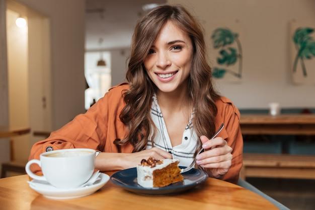 Ritratto di una donna allegra che mangia la fetta di torta