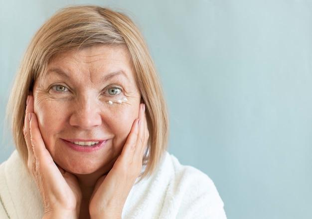 Ritratto di una donna allegra matura allegra seniora con crema antietà. trattamenti termali naturali, concetto di cura del viso. anti invecchiamento concetto. posto per il testo