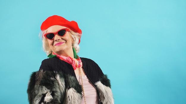 Ritratto di una donna anziana allegra in occhiali da sole