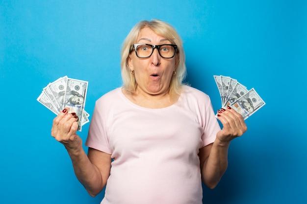 Ritratto di una donna anziana amichevole con una faccia sorpresa in una maglietta casual e occhiali con in mano i soldi su una parete blu isolata. volto emotivo. ricchezza del concetto, vittoria, prestito, pensione