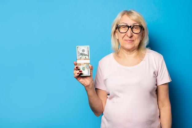 Ritratto di una donna anziana amichevole in t-shirt casual e bicchieri in possesso di denaro nelle sue mani su un muro blu isolato. volto emotivo. ricchezza del concetto, vittoria, credito, pensione