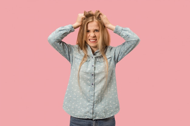 Ritratto di una donna arrabbiata isolata su una parete rosa
