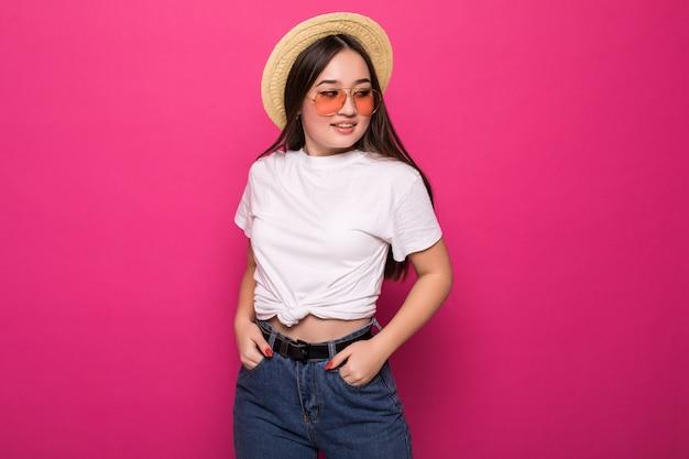 Ritratto di una donna asiatica allegra sopra la parete rosa
